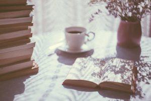 pile of books next to warm tea