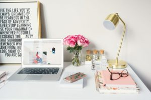 macbook air beside gold study lamp and spiral notebooks with motivational print in background desk aesthetic