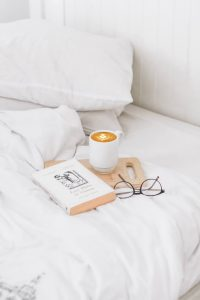 book, glasses and coffee on white duvet and pillow set