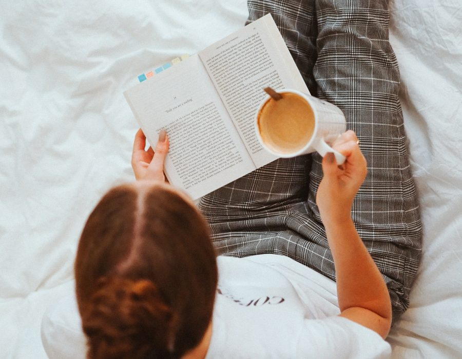 woman reading on bed with cup of tea cosy
