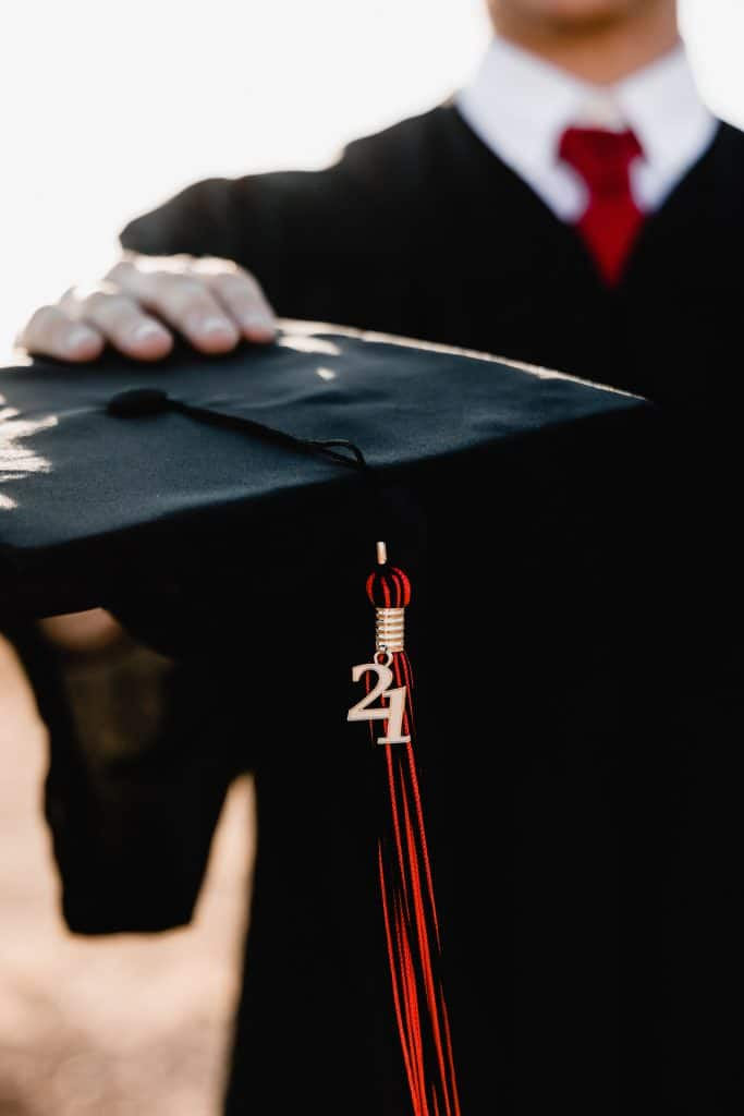 realities of life as a graduate in 2021. man holding graduate cap close to camera.