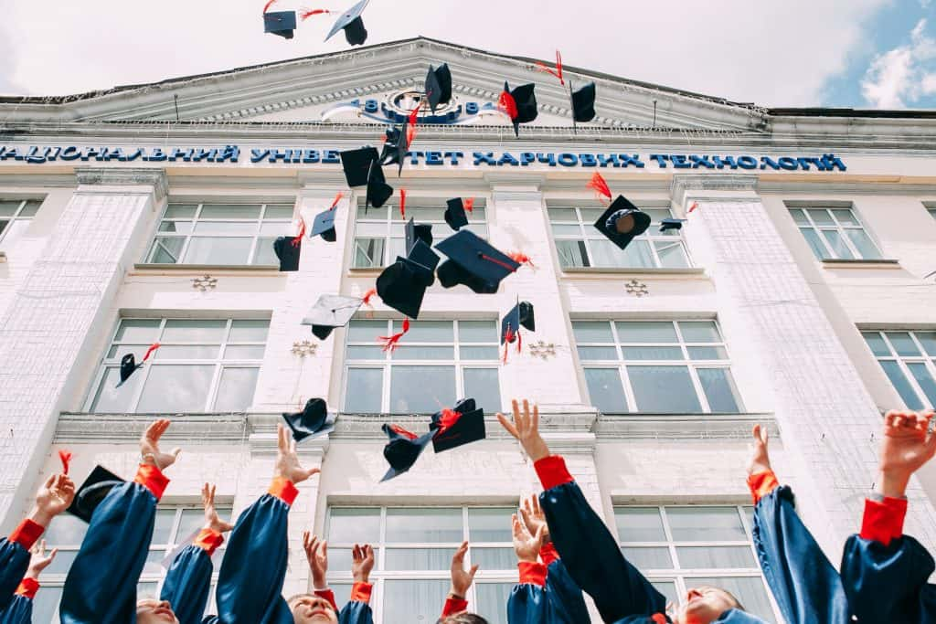 realities of life as a graduate in 2021. students throwing caps in the air outside building